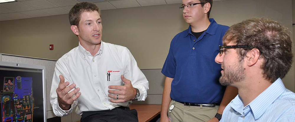 Industry engineer talking with Behrend students at computer